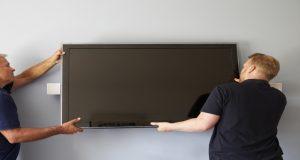 Вешают телевизон на стену из гипса